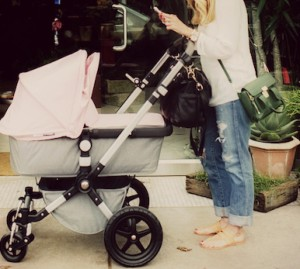A woman stands behind her stroller, while using her phone