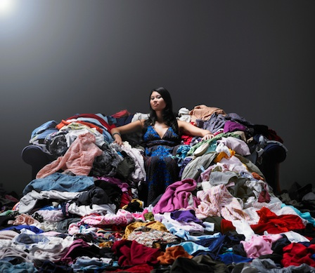 A woman sits on a couch among clothes piled up high around her